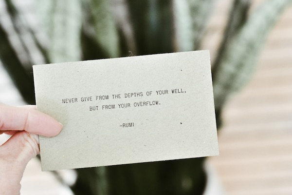 """Never give from the depths of your well, but from your overflow."" Rumi quote on card."